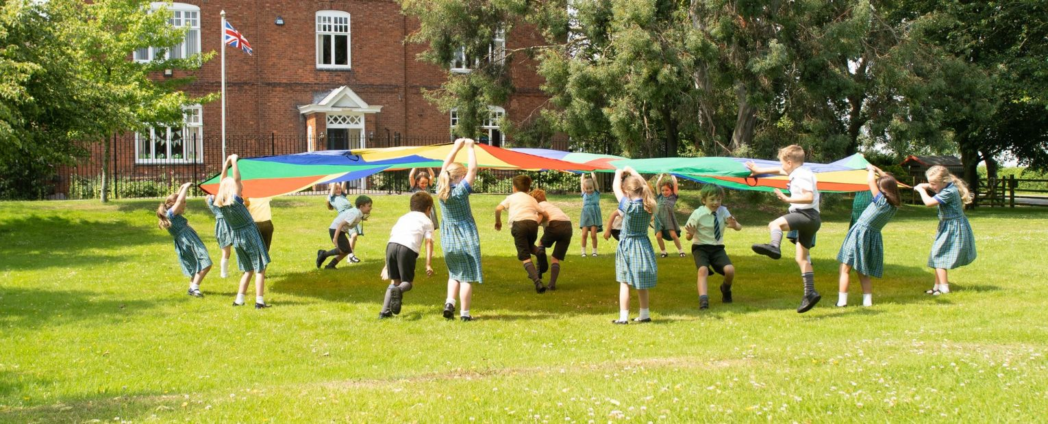 school children playing with a parachute