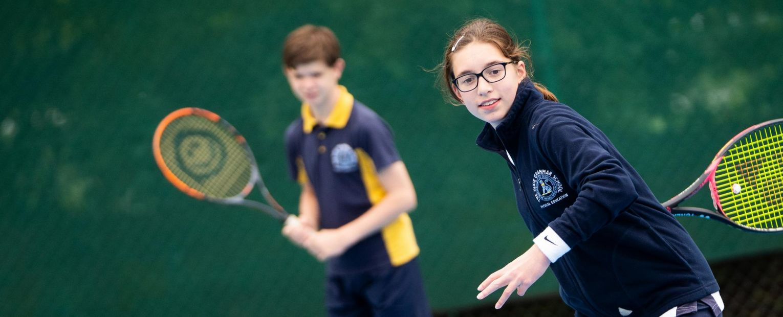 school children playing tennis