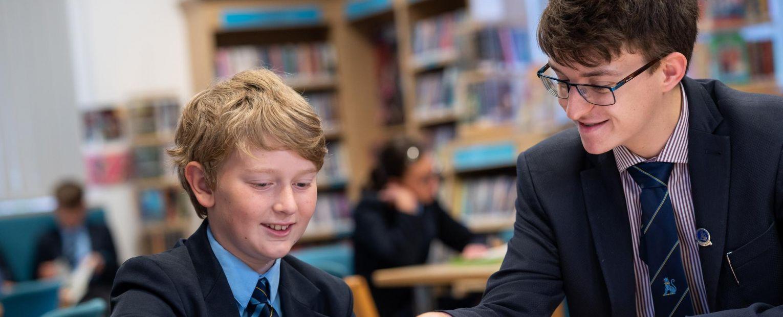 older school boy helping younger school boy