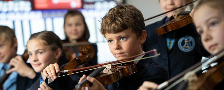 school children playing string instruments
